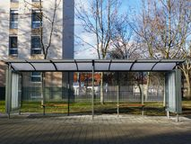 Modern glass and aluminum bus shelter in urban setting with paved concrete sidewalk stock photography