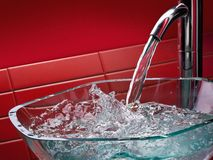 Modern glass bathroom sink. With running water and red tiles Stock Photos