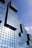 Modern glass building. Modern geometric city building reflecting sun and clouds Royalty Free Stock Image