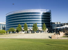 Modern Glass Building. Curved modern glass building with trees and grass in front Royalty Free Stock Images