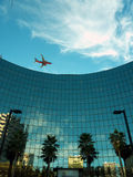 Modern glass building, plane above. A modern glass building in downtown, blue sky and a plane above, getting ready to land. Palm trees and reflections of other Stock Photo