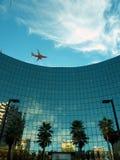 Modern glass building, plane above stock photo