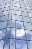 Modern glass building with reflections of blue sky and clouds Royalty Free Stock Photo