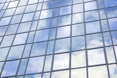 Modern glass building with reflections of blue sky and clouds Royalty Free Stock Photography