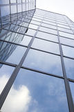 Modern glass building with reflections of blue sky and clouds Stock Images