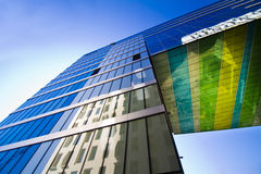 Modern glass building and sky. A new colorful glass building in downtown Oslo, Norway summer of 2012. The building is a part of the bar-code-architecture by the Royalty Free Stock Photos