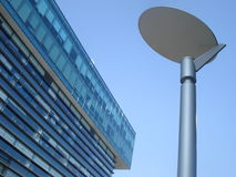 Modern glass building top and lamppost stock image