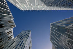 Modern glass buildings. Looking up at the sky surrounded by modern glass buildings Royalty Free Stock Photo