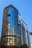 Modern glass byggnad med reflexioner och blå himmel Arkivfoto