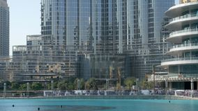 Modern glass and concrete building near fountains in sunny day, Dubai. Base of Burj Khalifa tower stock footage
