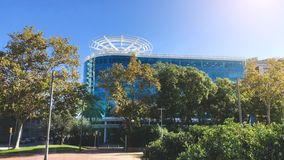 Modern glass facade. Office building with trees. Modern glass facade in trees. Office building at sunny day in Barcelona stock photo