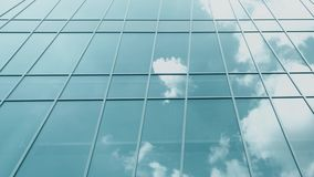 Modern glass facade windows reflect flying airplane and clouds, time lapse shot on Red camera stock video