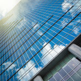 Modern glass hi-rise building skyscraper over blue bright sky Royalty Free Stock Photography