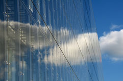 Modern glass office building. The clouds reflect from the  glass of this modern glass office building Stock Image