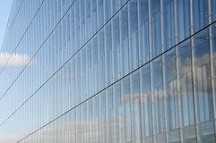 Modern glass office building. The clouds reflect from the  glass of this modern glass office building Royalty Free Stock Photo