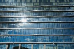 Modern glass office building at sun. Modern glass office building with sky sun and clouds reflection royalty free stock image