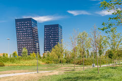 Modern glass office buildings in the green field with cloudy sky background. Stock Images