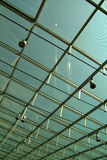 Modern glass roof. Background looking up to modern glass roof with light fittings Stock Photos