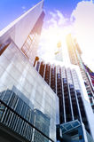 Modern glass silhouettes of skyscrapers in the city and dramatic sunlight Stock Image