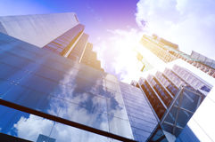 Modern glass silhouettes of skyscrapers in the city and dramatic sunlight Stock Photography