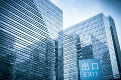 Modern glass skyscraper with garage exit traffic sign Royalty Free Stock Images