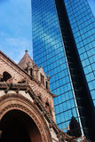 Modern glass skyscraper and the old church Stock Images