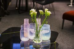 Modern glass vases in different shades, pink, white, blue, with flowers standing in the interior royalty free stock images