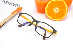 Modern Glasses and Notepad Nearing a group of Orange Royalty Free Stock Image