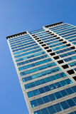 Modern glassy skyscraper against the blue sky. Bottom view on the skyscraper Royalty Free Stock Photo