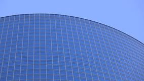 Modern glassy skyscraper top against blue sky. Modern glassy skyscraper top against sky royalty free stock photography