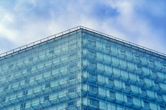 Modern glossy facade of building against of the cloudy sky. Multilayer facade system of a high-rise building. Spider facade fixing system. Symmetry composition Stock Photography