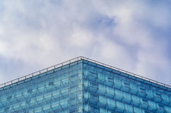 Modern glossy facade of building against of the cloudy sky. Multilayer facade system of a high-rise building. Spider facade fixing system. Symmetry composition Royalty Free Stock Photography