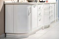 Modern gourmet kitchen interior. Beautiful white kitchen furniture stock photography