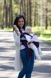 Modern går med spädbarnet behandla som ett barn Arkivfoton
