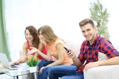 Modern grabb med en smartphone och hans vänner som sitter på soffan arkivfoton