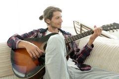 Modern grabb med gitarrsammanträde på soffan i vardagsrum Arkivbilder