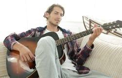 Modern grabb med gitarrsammanträde på soffan i vardagsrum Arkivfoto