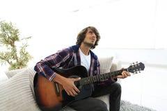 Modern grabb som spelar gitarrsammanträde på soffan begrepp av en livsstil arkivbild