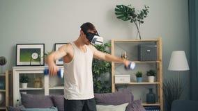 Modern grabbidrottsmanutbildning med hantlar hemma som bär bara ar-exponeringsglas stock video