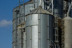 Modern grain terminal. Metal tanks of elevator. Grain-drying complex construction. Commercial grain or seed silos at Royalty Free Stock Image