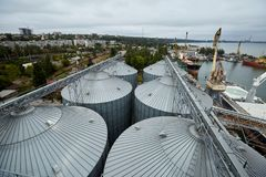 Modern grain terminal. Metal tanks of elevator. Grain-drying complex construction. Commercial grain or seed silos at Royalty Free Stock Photos