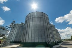The modern granary. High metal silos for storage of wheat and barley. Sunny day, the blue sky. Industrial landscape Stock Photos