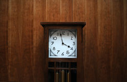 Modern grandfather clock against wooden wall Stock Photography