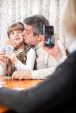 Modern grandmother photographing grandfather and granddaughter w Royalty Free Stock Image