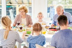 Modern Grandparents Enjoying Family Dinner. Portrait of happy family enjoying dinner together sitting round festive table with delicious dishes during holiday royalty free stock photography