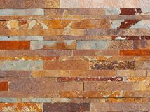 Modern granite stone wall, made of bricks of different shades of colors from gray to red stock photos