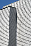 Modern Gray Building With Shingles. And angles forms an abstract linear design against a blue sky Stock Photos