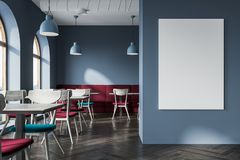 Modern gray cafe interior, a poster close up. Modern gray cafe interior with a wooden floor, and square tables with blue chairs near them. Soft red sofas along Royalty Free Stock Images