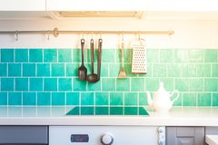 Kitchen features dark gray flat front cabinets paired with white quartz countertops and a glossy blue care tile. Royalty Free Stock Photo