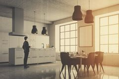 Gray kitchen corner, square windows, table, man Royalty Free Stock Photo
